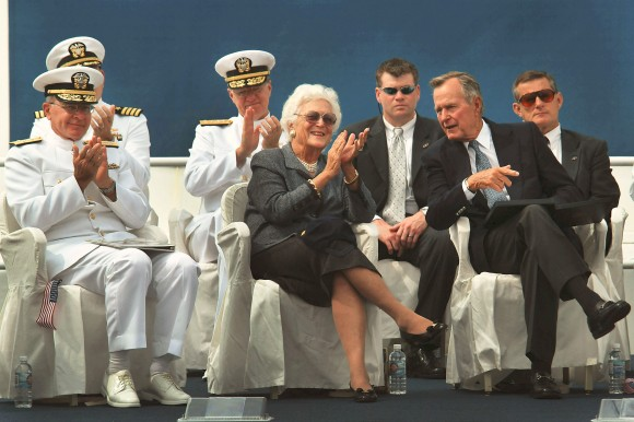 "030906-N-2383B-039 Newport News, Va. (Aug. 26, 2003) -- President George H.W. Bush and former First Lady Barbara Bush share applause with Adm. Vern Clark, Chief of Naval Operations (CNO), as they watch the Navy's parachute team ""The Leapfrogs"" perform during a keel laying ceremony honoring the building of the nuclear-powered aircraft carrier George H.W. Bush (CVN 77). This will be the 10th and final Nimitz-class aircraft carrier as it undergoes the first of four ceremonial traditions that will happen throughout the life of the warship. U.S. Navy photo by Chief Photographer's Mate Johnny Bivera. (RELEASED)."